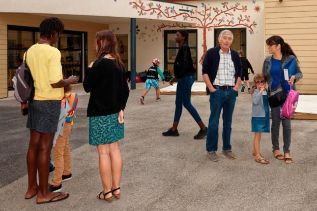 Elèves et parents se pressent dans la cours de l'école sous l'oeil bienveillant de notre maire